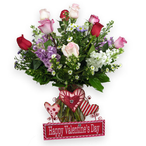 Light Pink, Lavender, and Red Roses are the focal point of this gorgeous bouquet. Lavender and white stock, purple and white Monte Casino aster, along with lemon leaf greens are presented in an upgraded clear vase and adorned with a metal decor HVD sign.<br/><br/>  